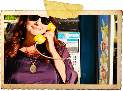 Laura holding up a phone in a phone booth